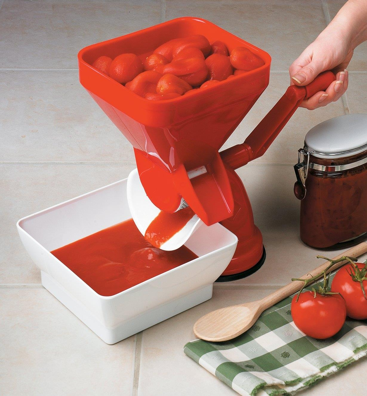 Turning the handle to process whole tomatoes into pulp that is extracted into a catch bowl