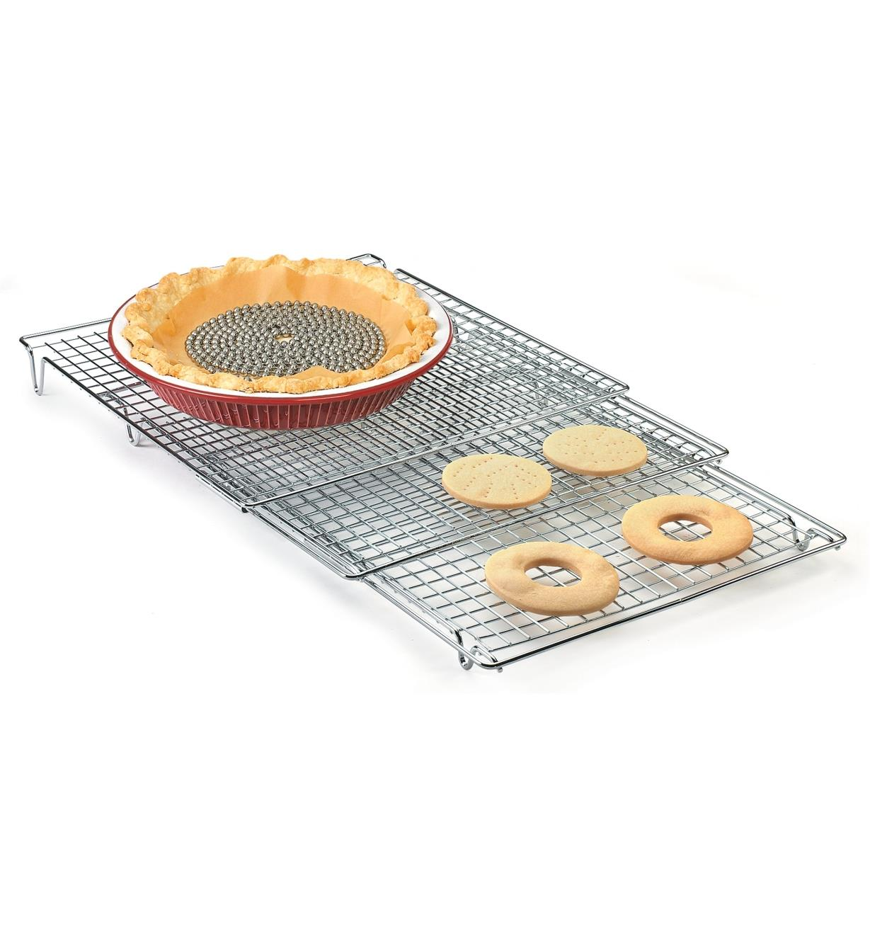 A pie crust and cookies cooling on an Expandable Cooling Rack