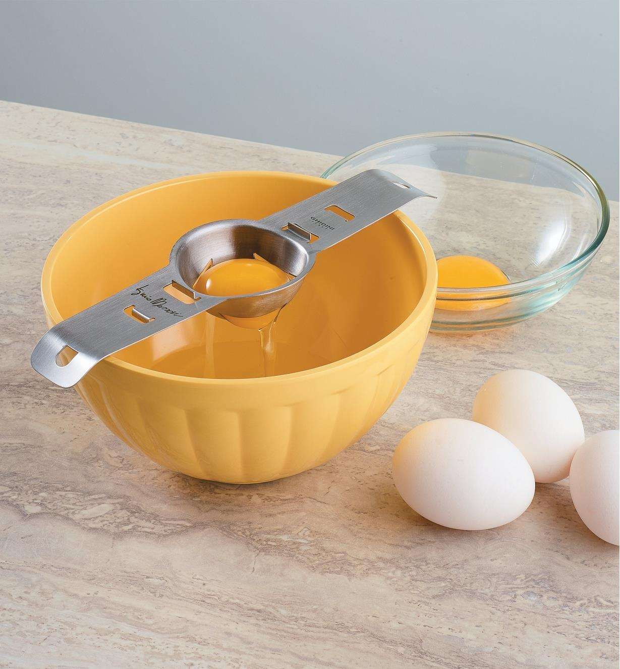 Egg separator sits on a bowl, with a yolk in the slotted cup and egg white underneath in the bowl