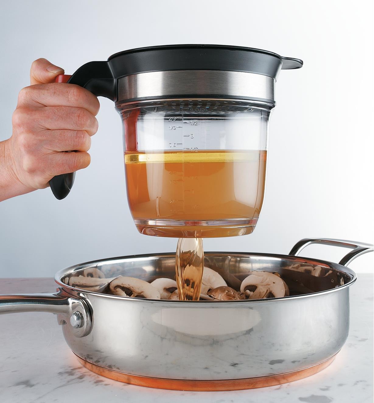 Personne versant du jus de cuisson dans une casserole de champignons avec une tasse à dégraisser