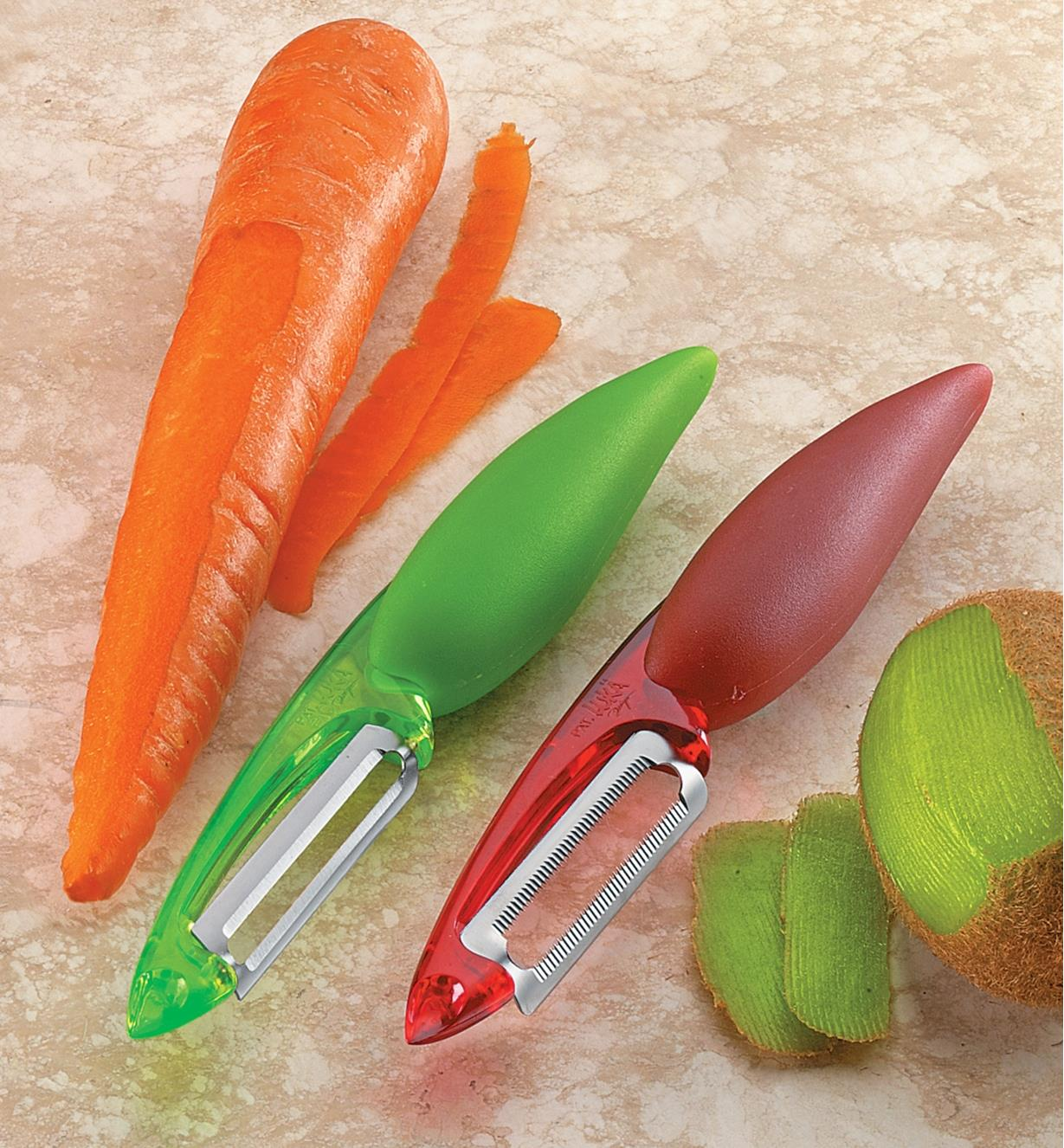 Set of two peelers on a counter beside carrot and kiwi that have just been peeled
