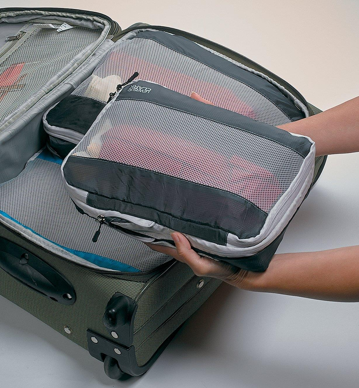 Placing filled Expandable Packing Cubes in a suitcase
