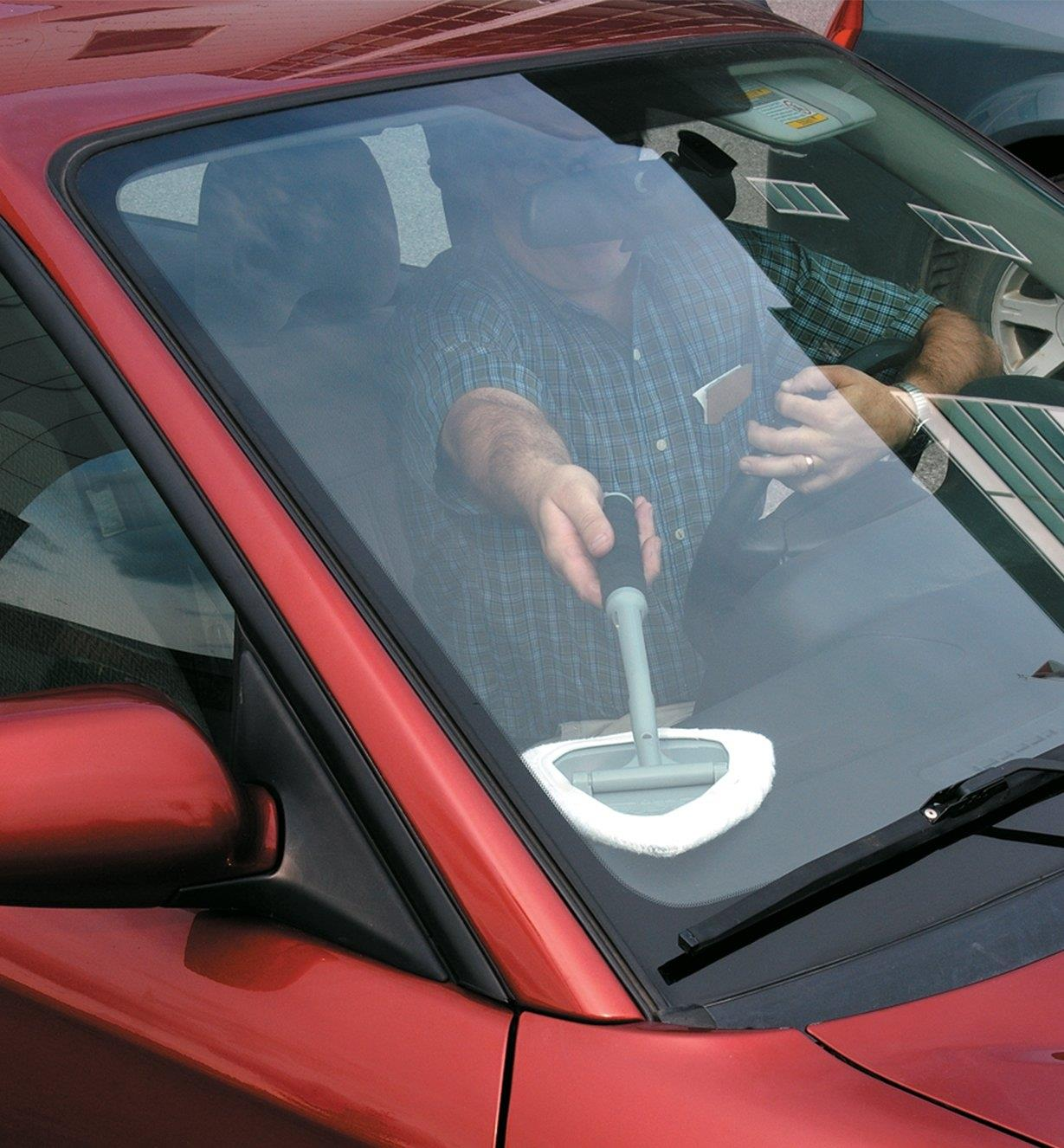 Using the Glass and Surface Cleaner to wash the inside corner of a car windshield