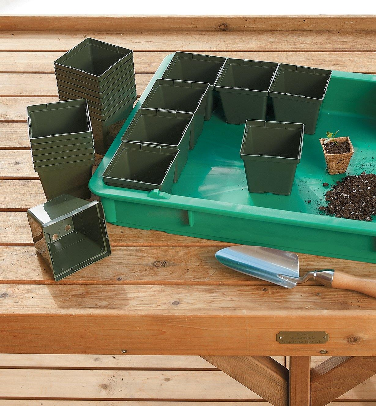 Giant Plant Tray being filled with square plastic pots on a potting table