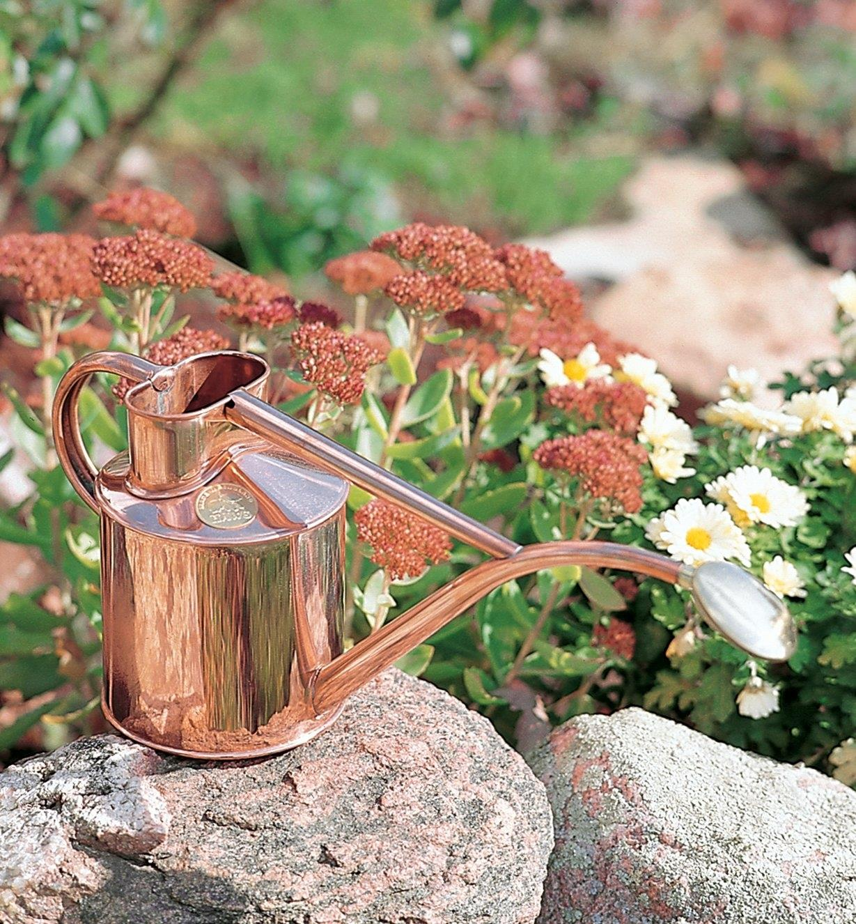 Haws Copper Watering Can sitting on a rock in a flower garden