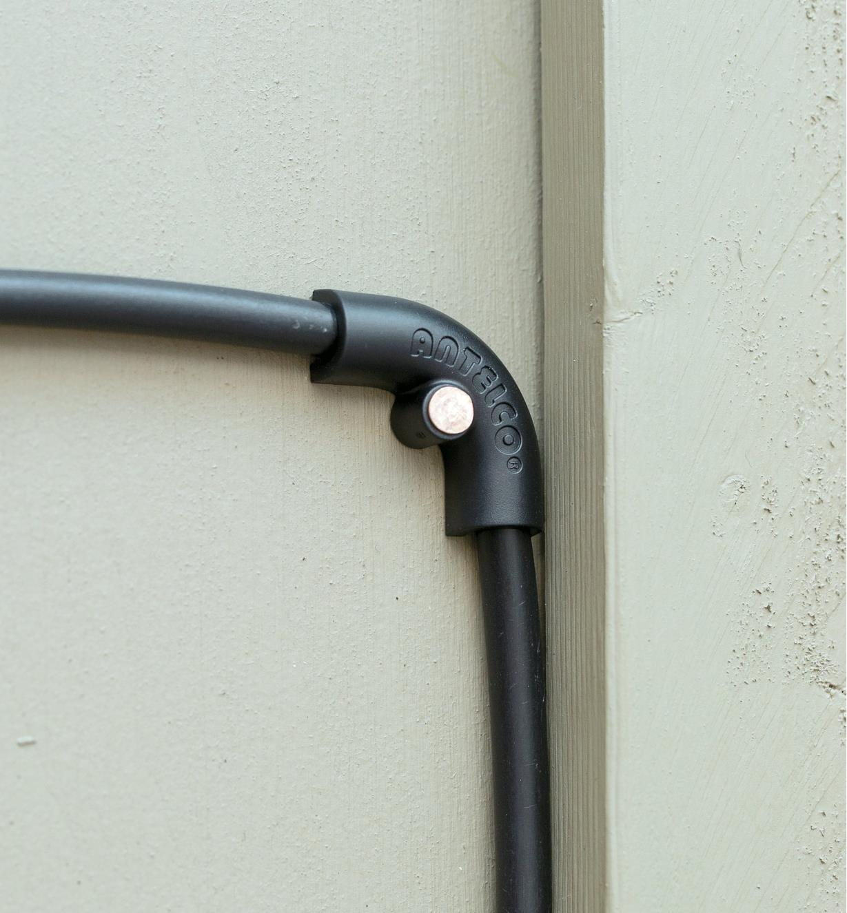 Clip-on elbow fitted onto irrigation hose and mounted on a fence