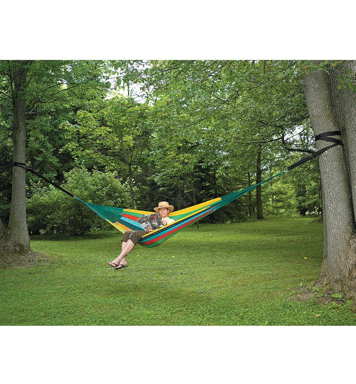 A woman relaxes in a hammock held between two trees by the Hammock Tree Straps