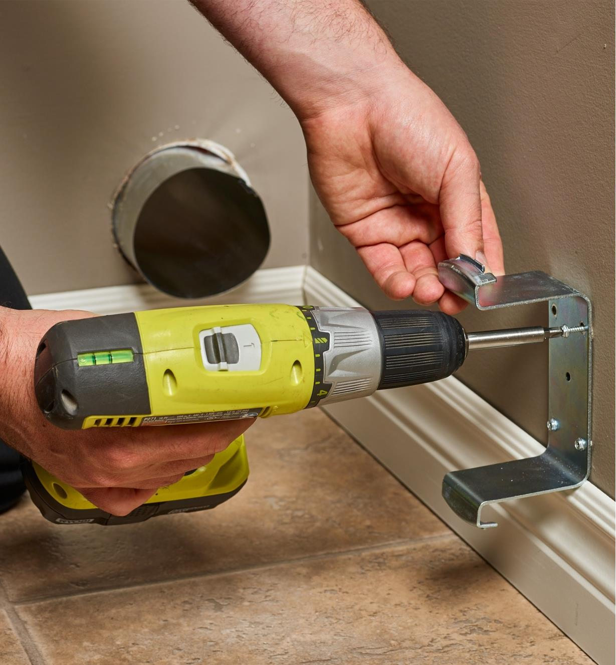 Attaching the bracket to the wall using a power drill