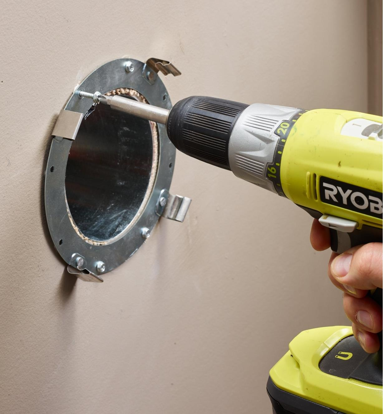 Attaching the steel collar to the wall using a power drill