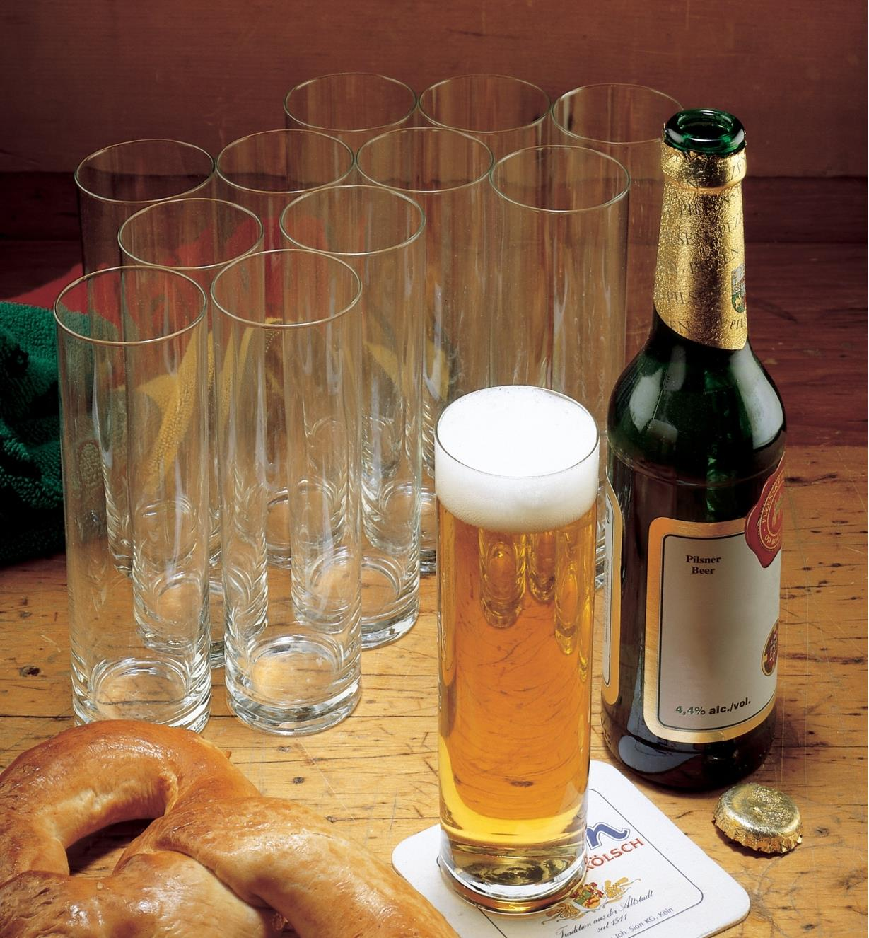 Set of 12 Kolsch glasses, one filled with beer next to a beer bottle