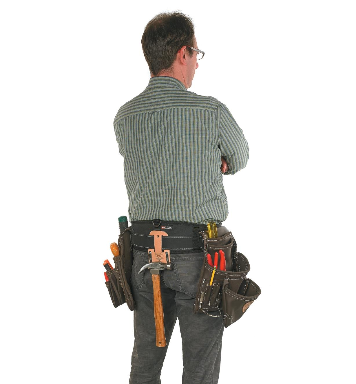 Back view of a man wearing the carpenter's four-piece apron set with the hammer holder at the back