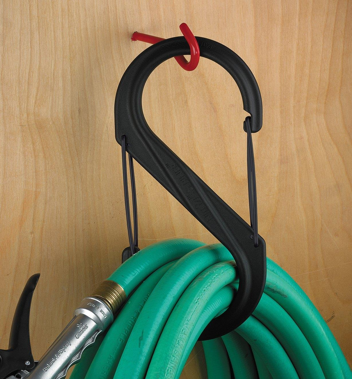 "A coiled garden hose held in a 10 1/2"" S-Biner hanging on a wall hook"