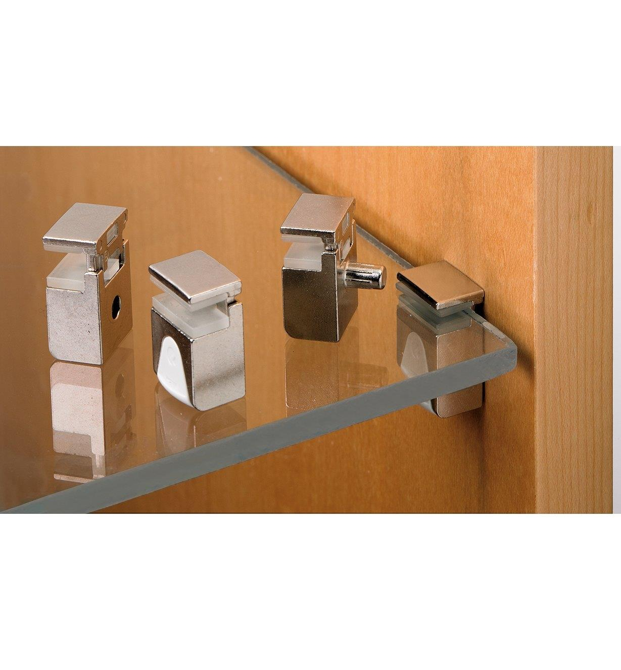 Three Kubic supports sitting on a glass shelf, with one support holding up the shelf