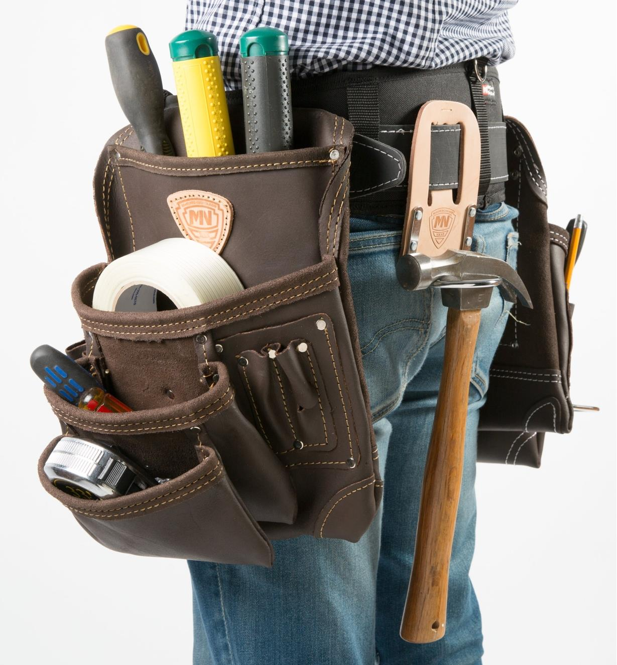 A man wearing a belt with two pouches and a hammer holder