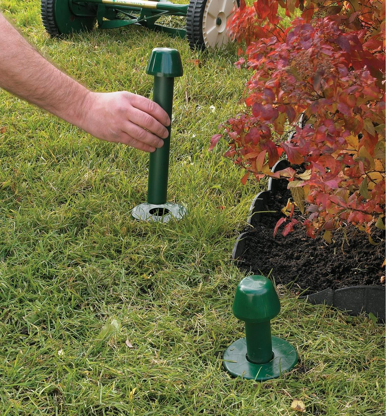 Inserting the hose guide into the base installed in a lawn