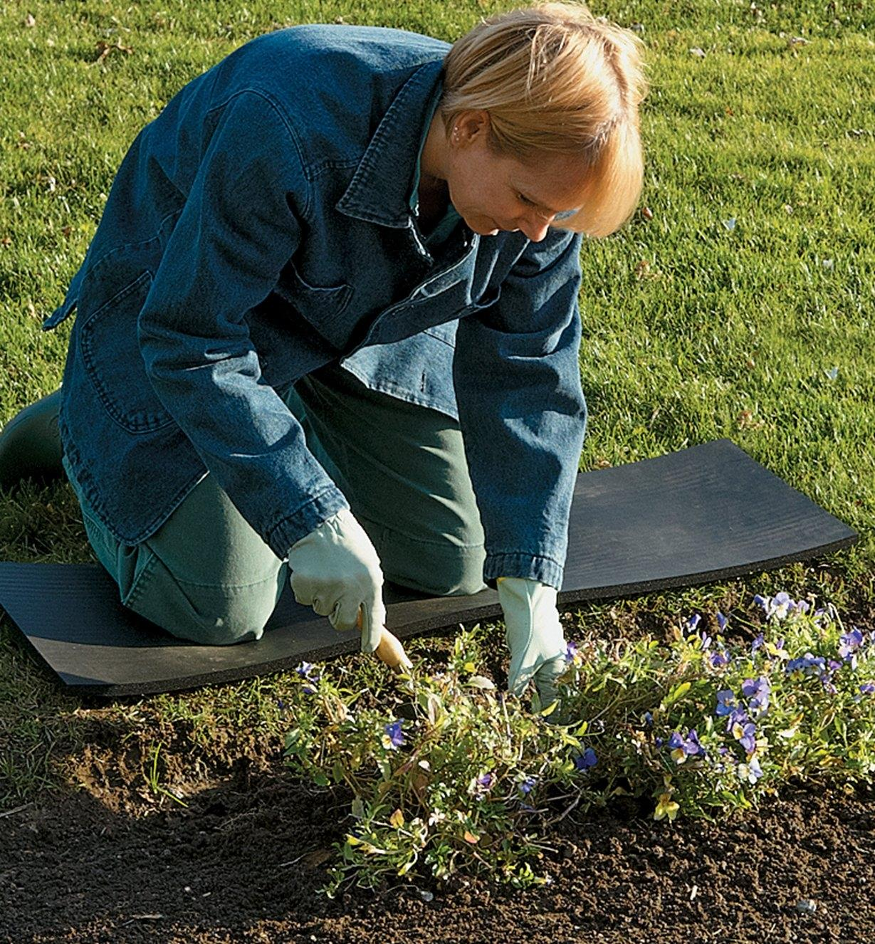 A woman kneels on on the Kneeling Strip while gardening