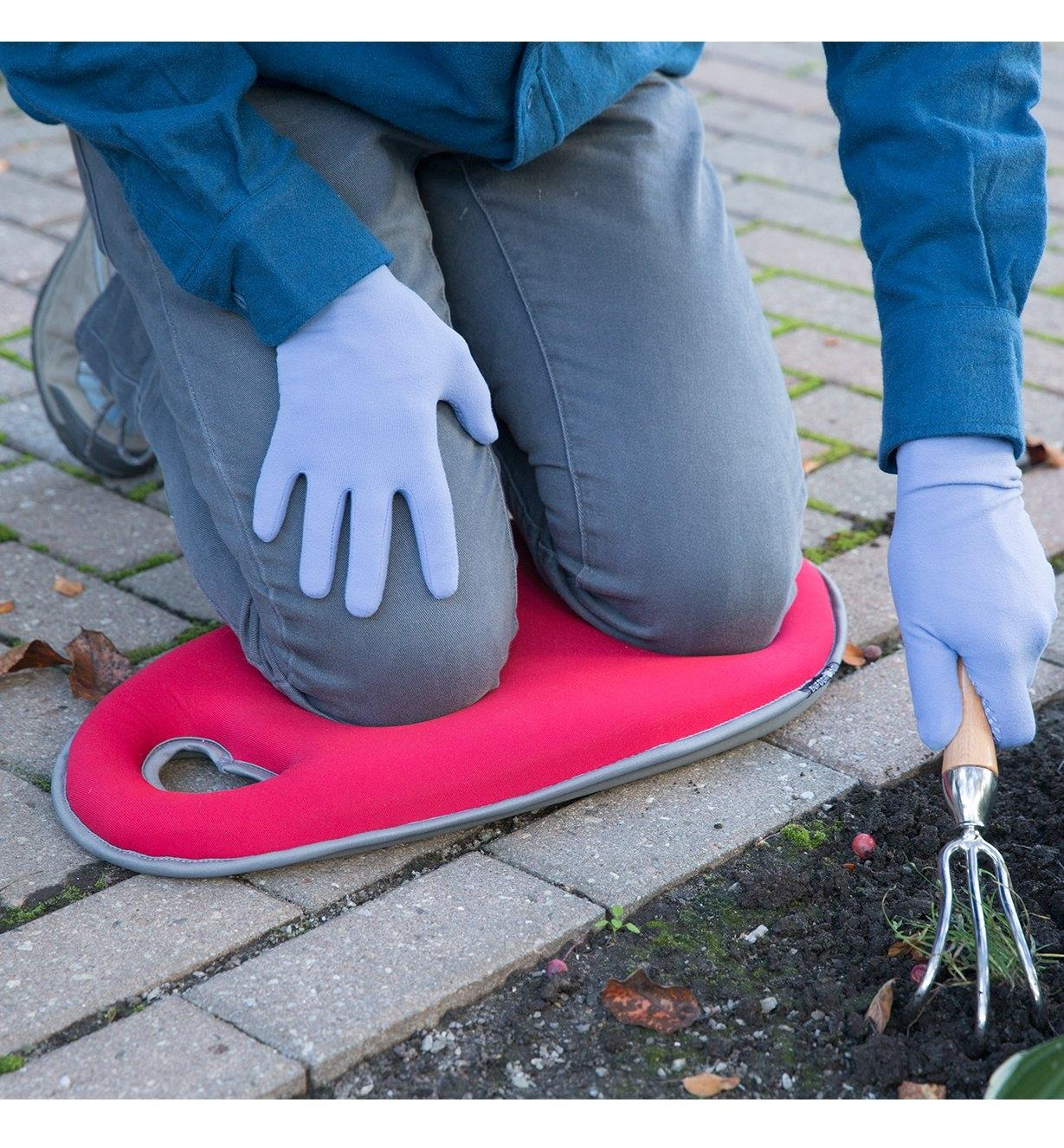 A person kneels on a Red Kneeling Pad while gardening