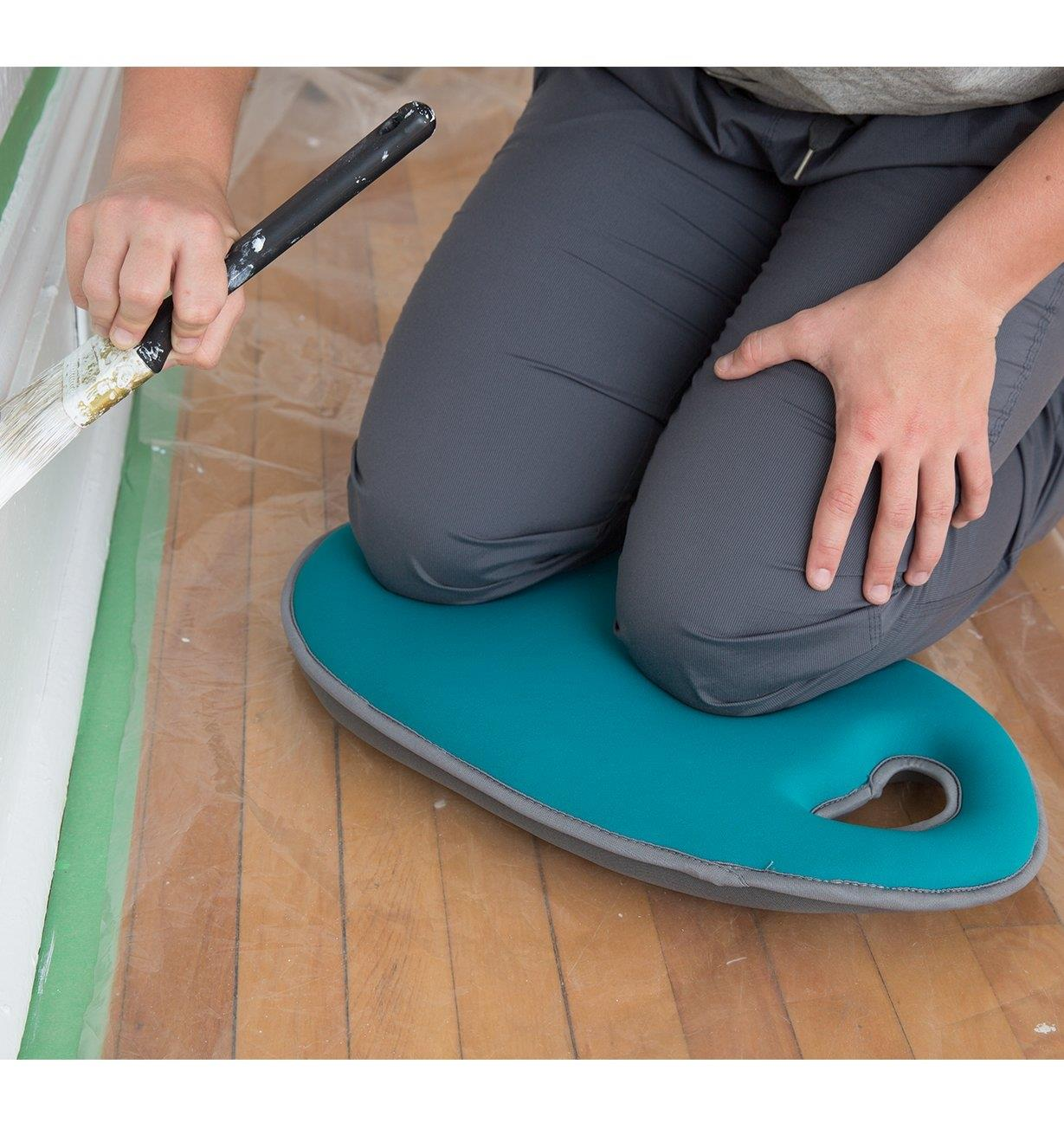 A person kneels on the Teal Kneeling Pad while painting trim in a house