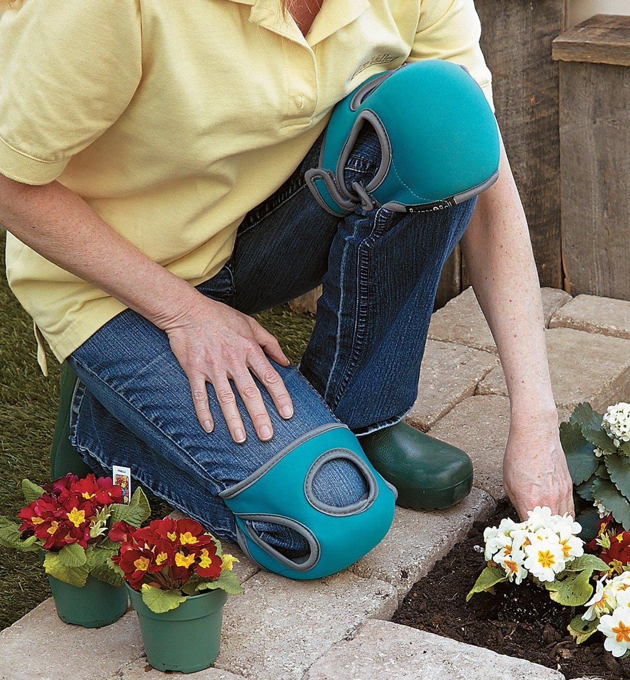 A woman wearing memory foam knee pads kneels to plant flowers in a garden bed