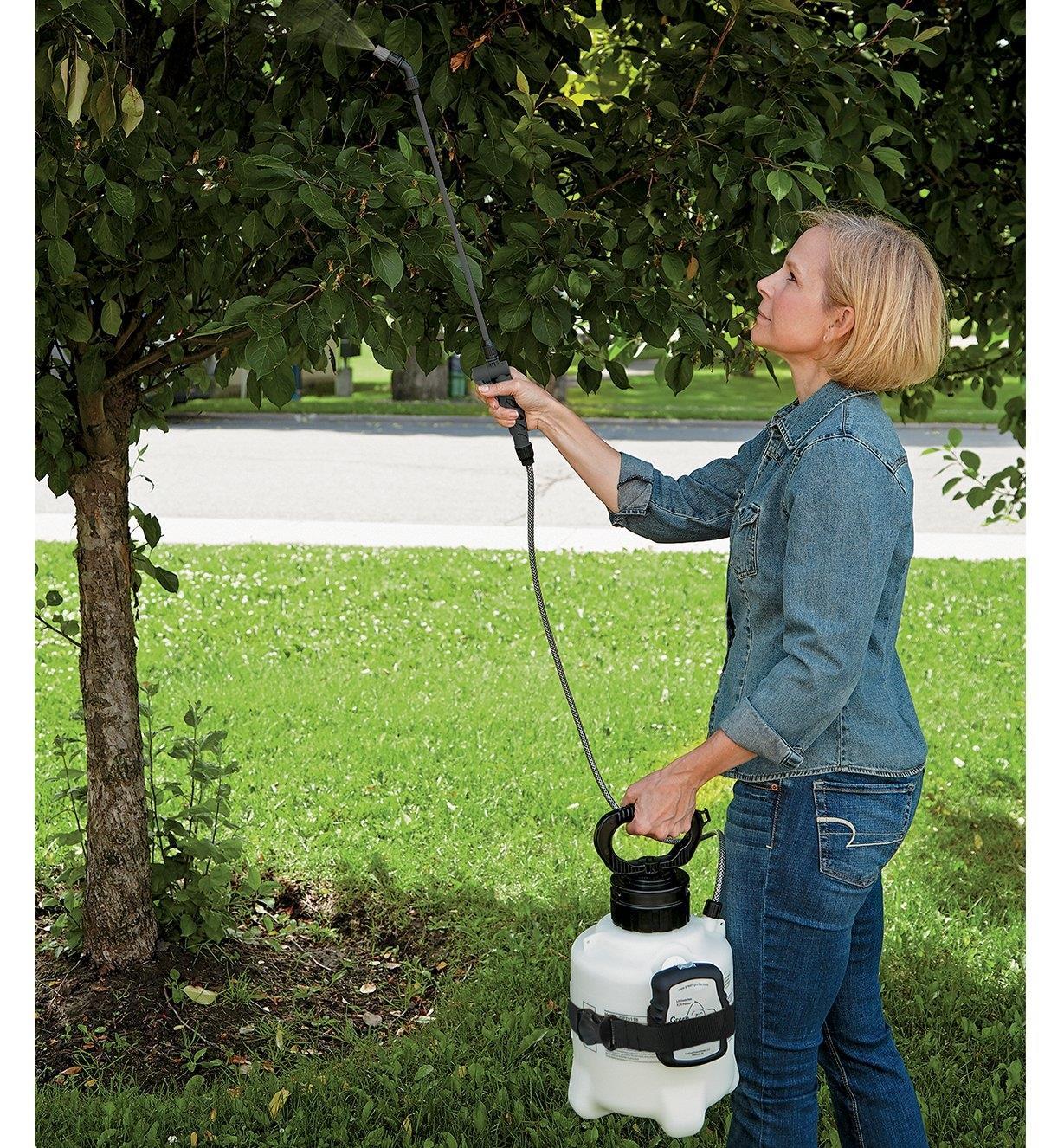 A woman sprays a tree using the Garden Sprayer