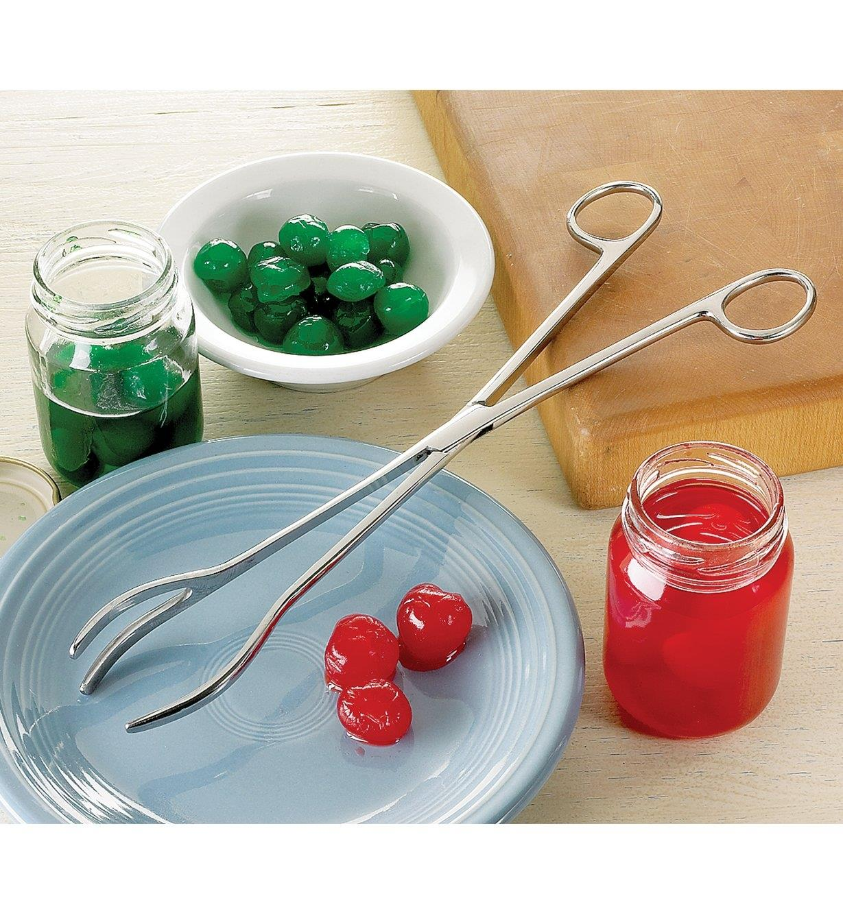 Kitchen Tongs resting on a plate beside two jars of maraschino cherries