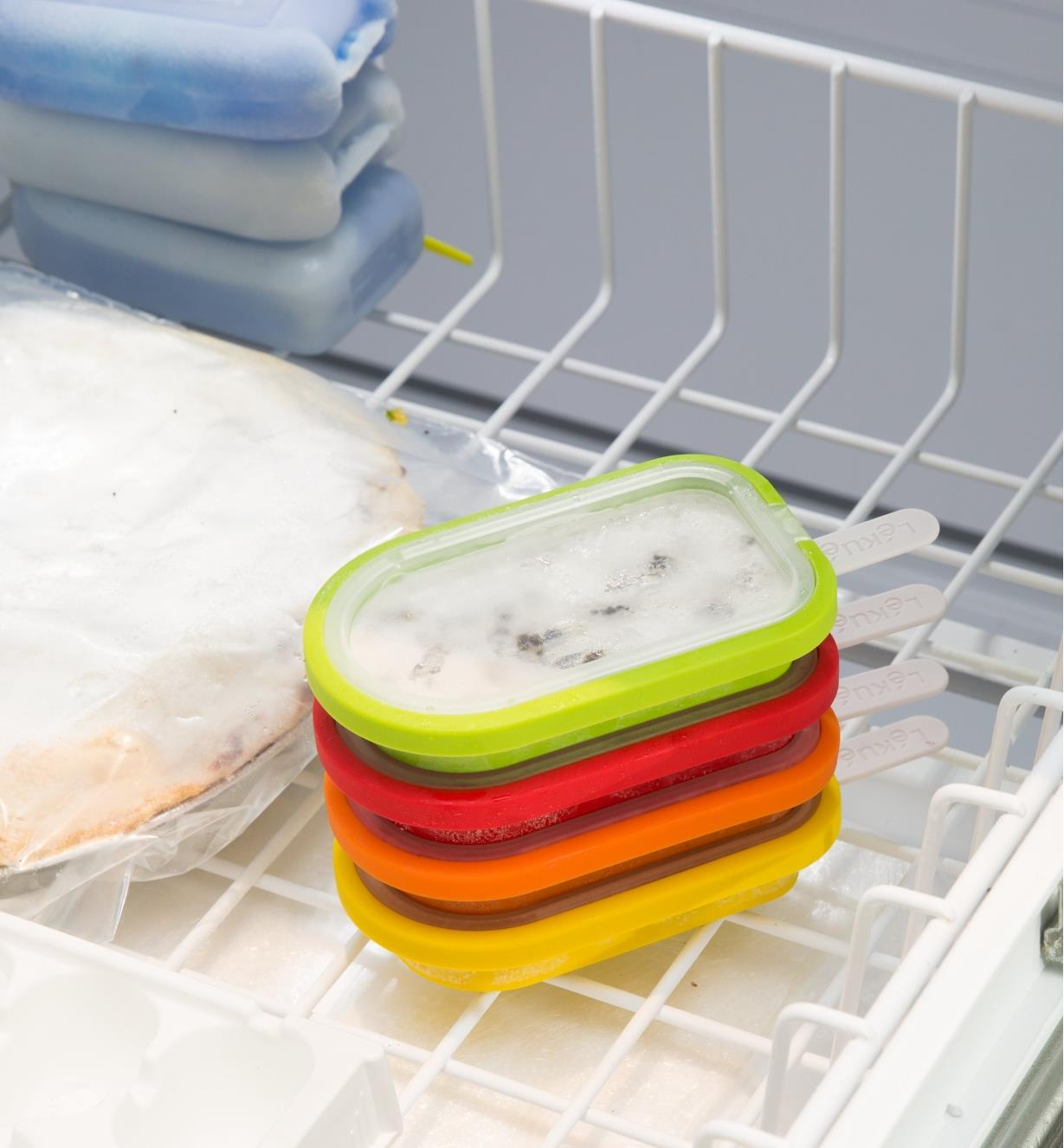 Ice pop molds stacked in a freezer drawer