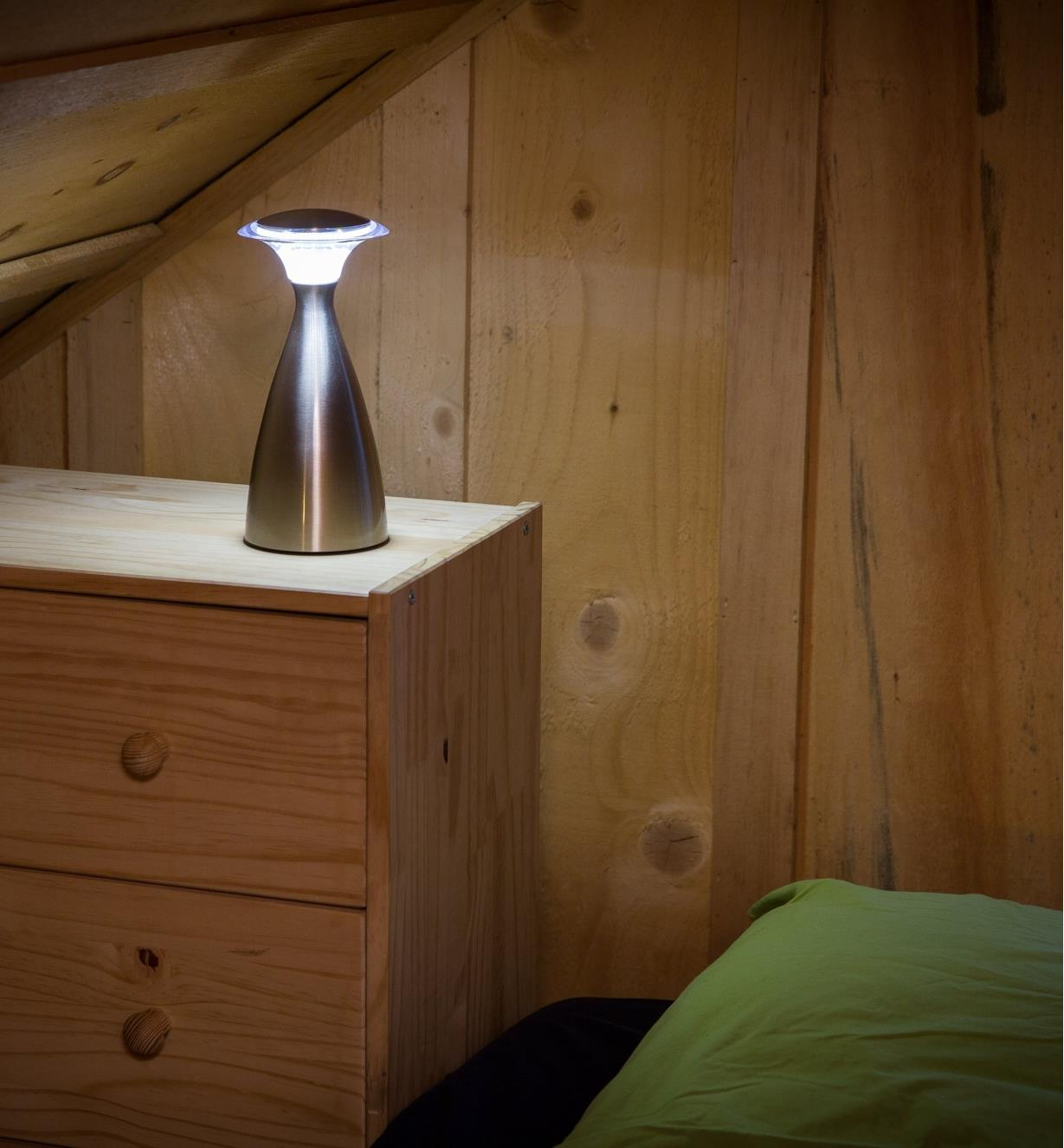 Lanterna Lamp on a dresser beside a bed
