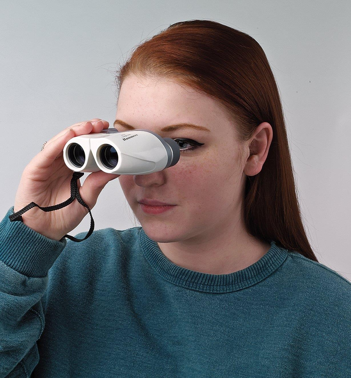 A young woman holds the Lightweight Compact Binoculars up to her eyes