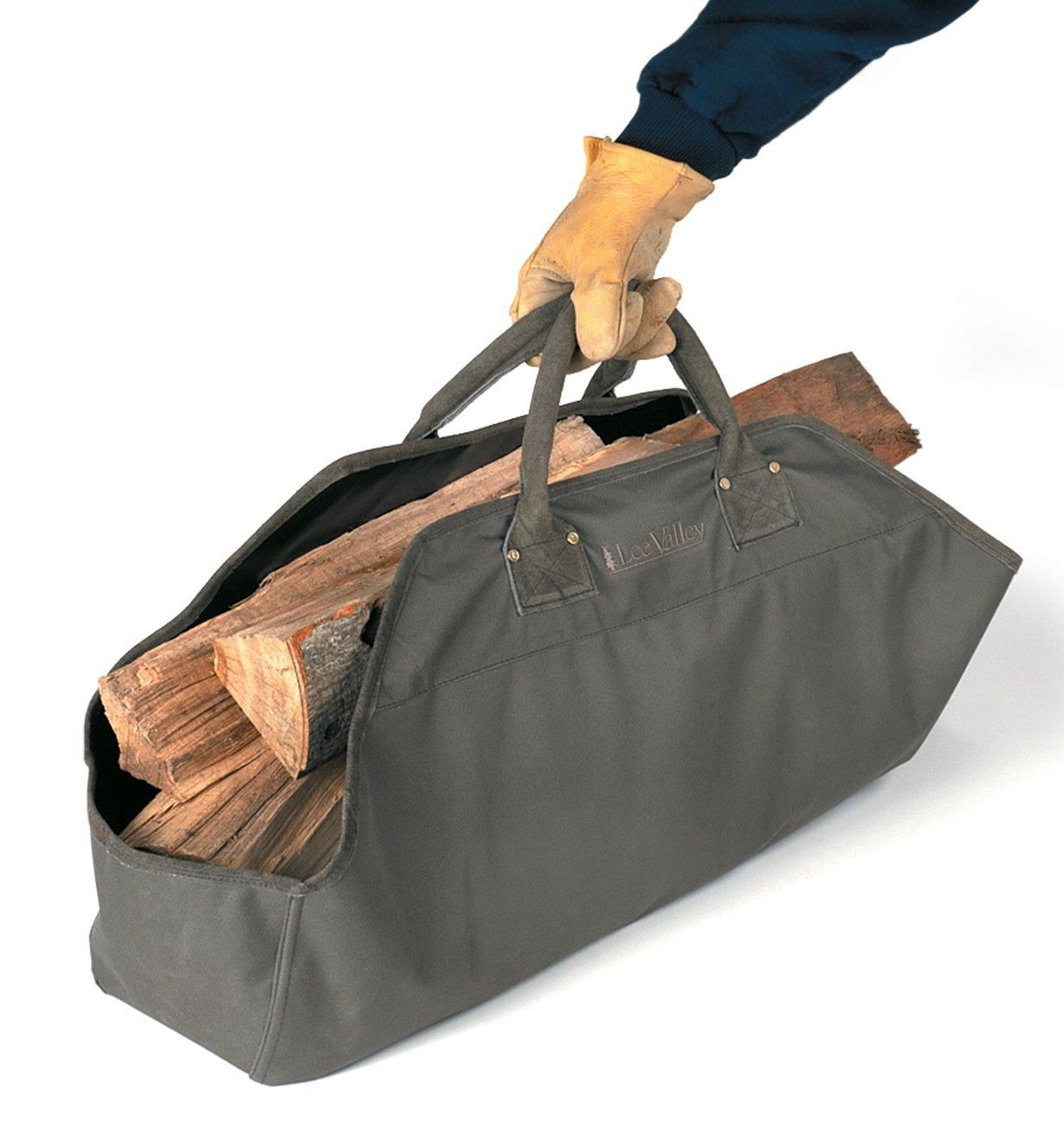 Lee Valley Firewood Tote filled with firewood, being picked up by the handles