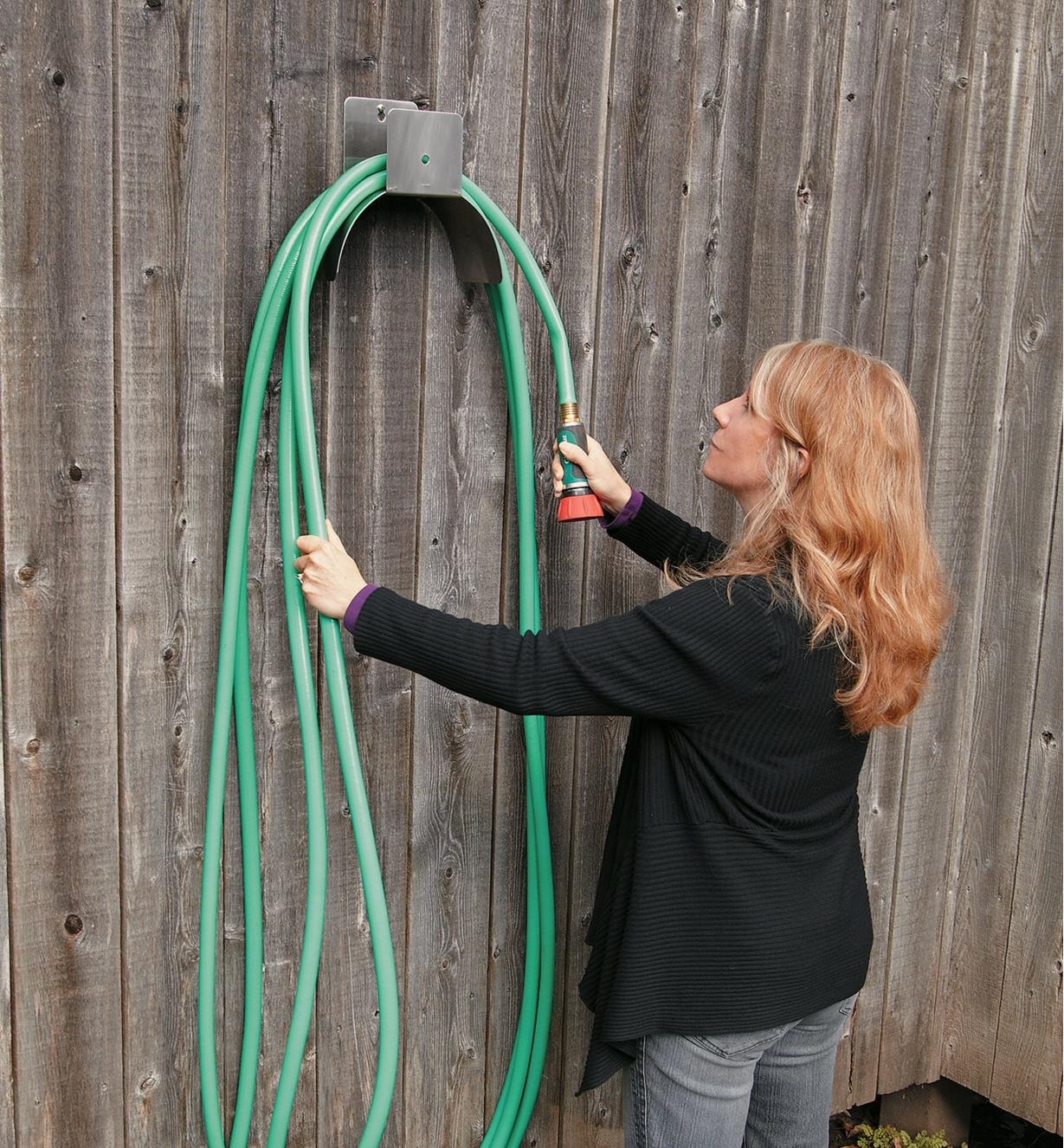 A woman loops a hose over the Hose Hanger