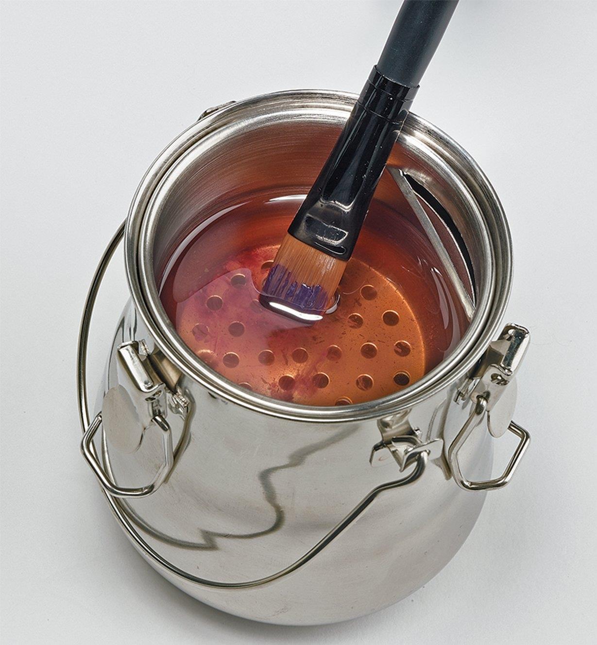 Pinceau d'artiste trempant dans un pot lave-pinceaux