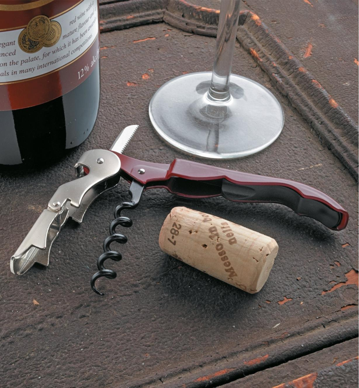 Pulltap Double-Lever Corkscrew lying next to a cork, a wine bottle and a glass