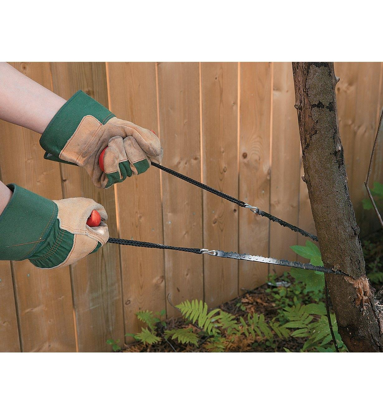 Using a Pocket Chain Saw to cut through a small tree trunk