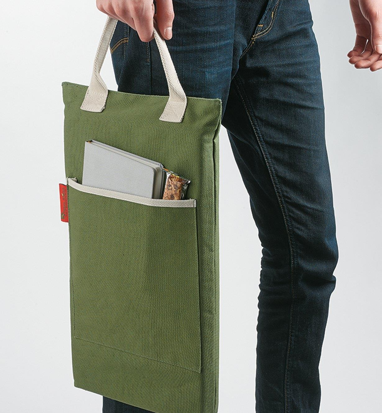 Carrying the Portable Canvas Utility Cushion by its handle