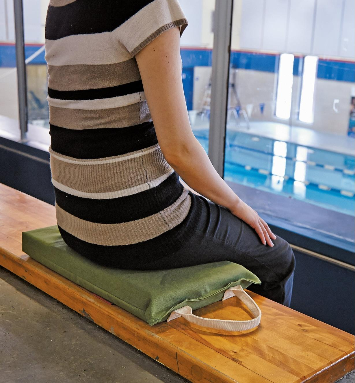 A woman sits on the Portable Canvas Utility Cushion on bleachers at a swimming pool