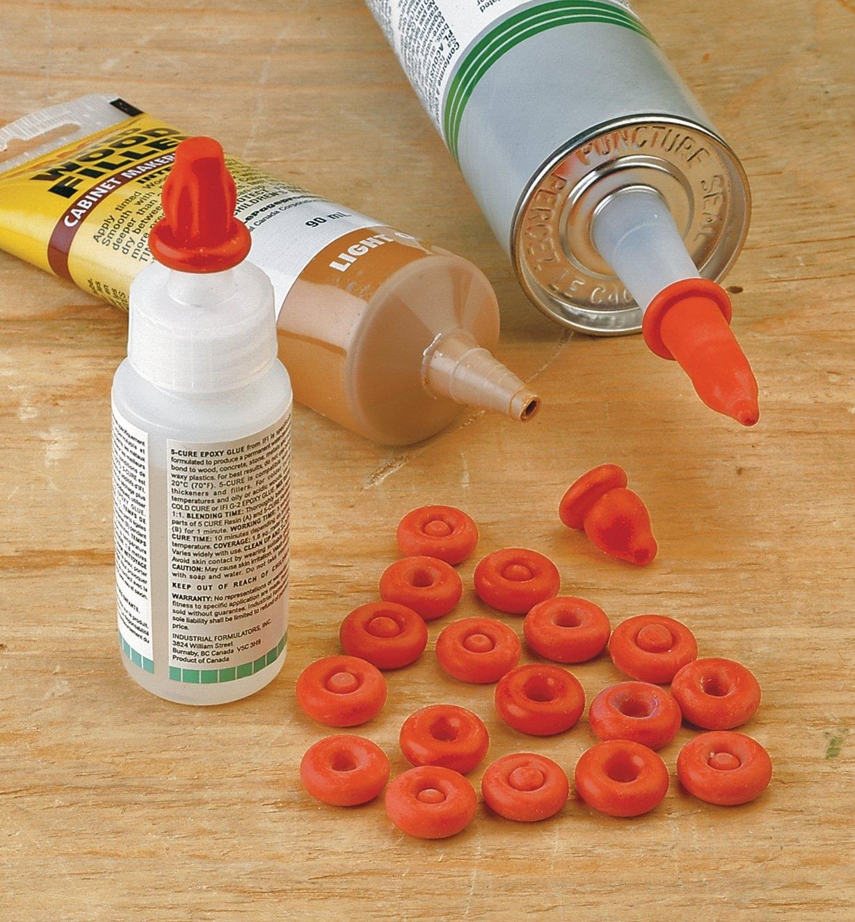 A caulking tube, a wood filer tube and a glue bottle using nozzle caps to seal their nozzles