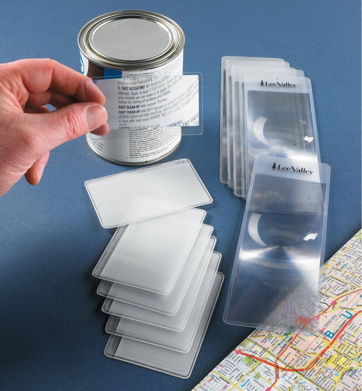 Six credit card magnifiers and six bookmark magnifiers spread on a table, beside a road map and a can with small writing on the back