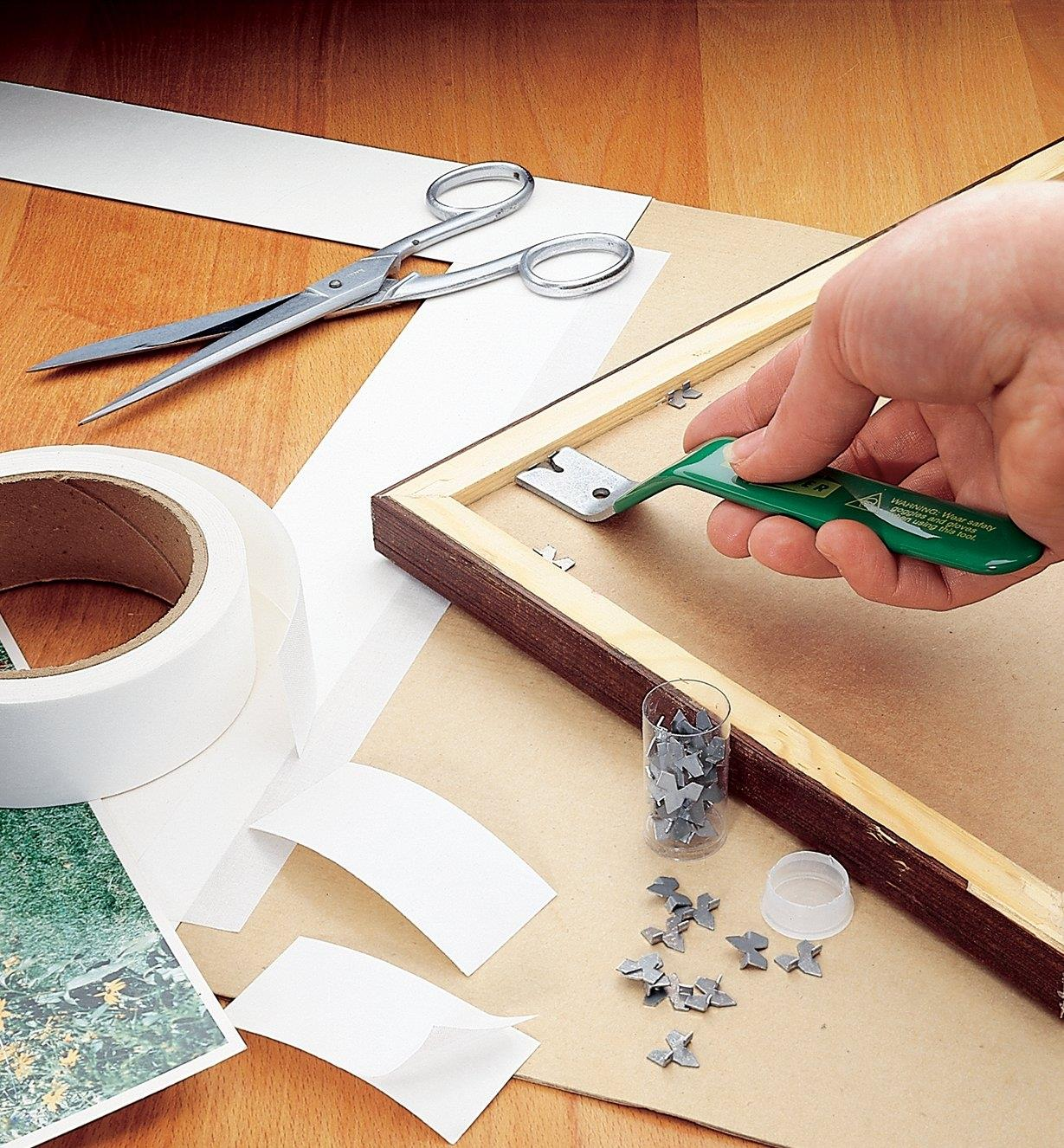 Driving glazier's points into a wooden picture frame with a PushMate Tool