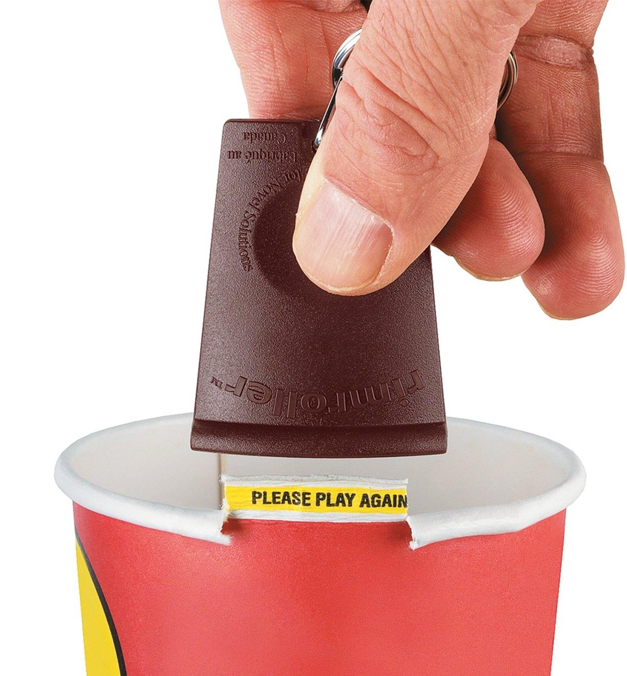 Pulling up the Rimroller to unroll the rim of the cup and reveal the message inside