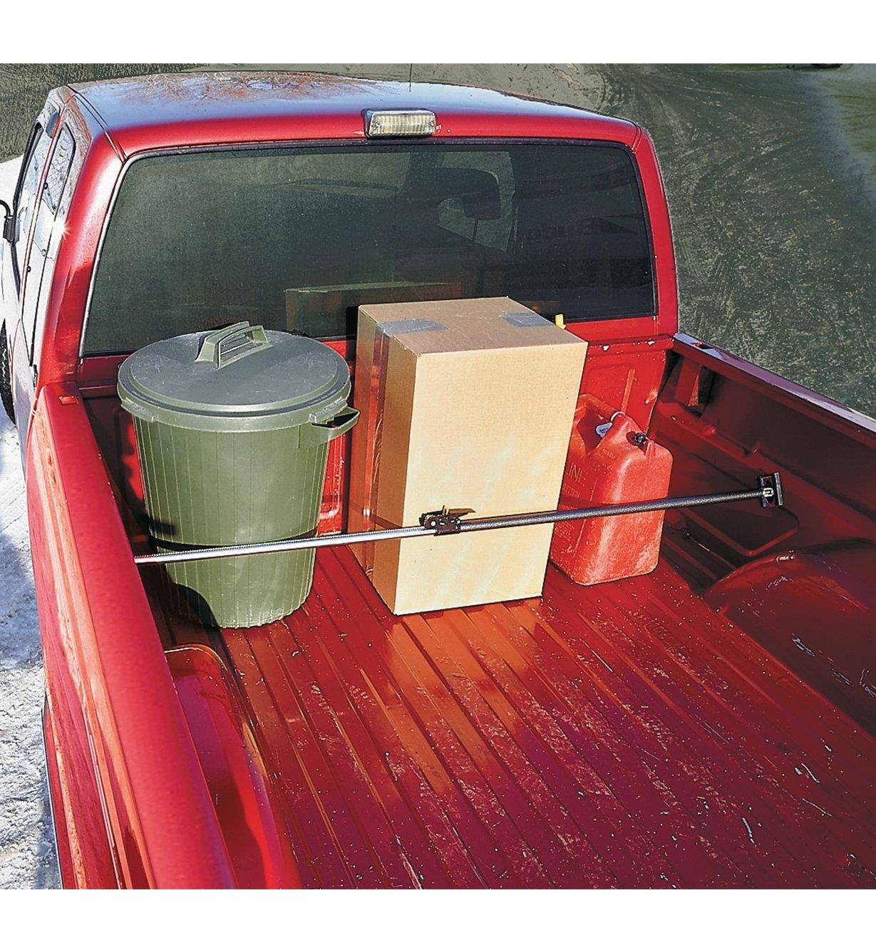 Ratcheting Cargo Bar installed in a truck bed, holding cargo in place