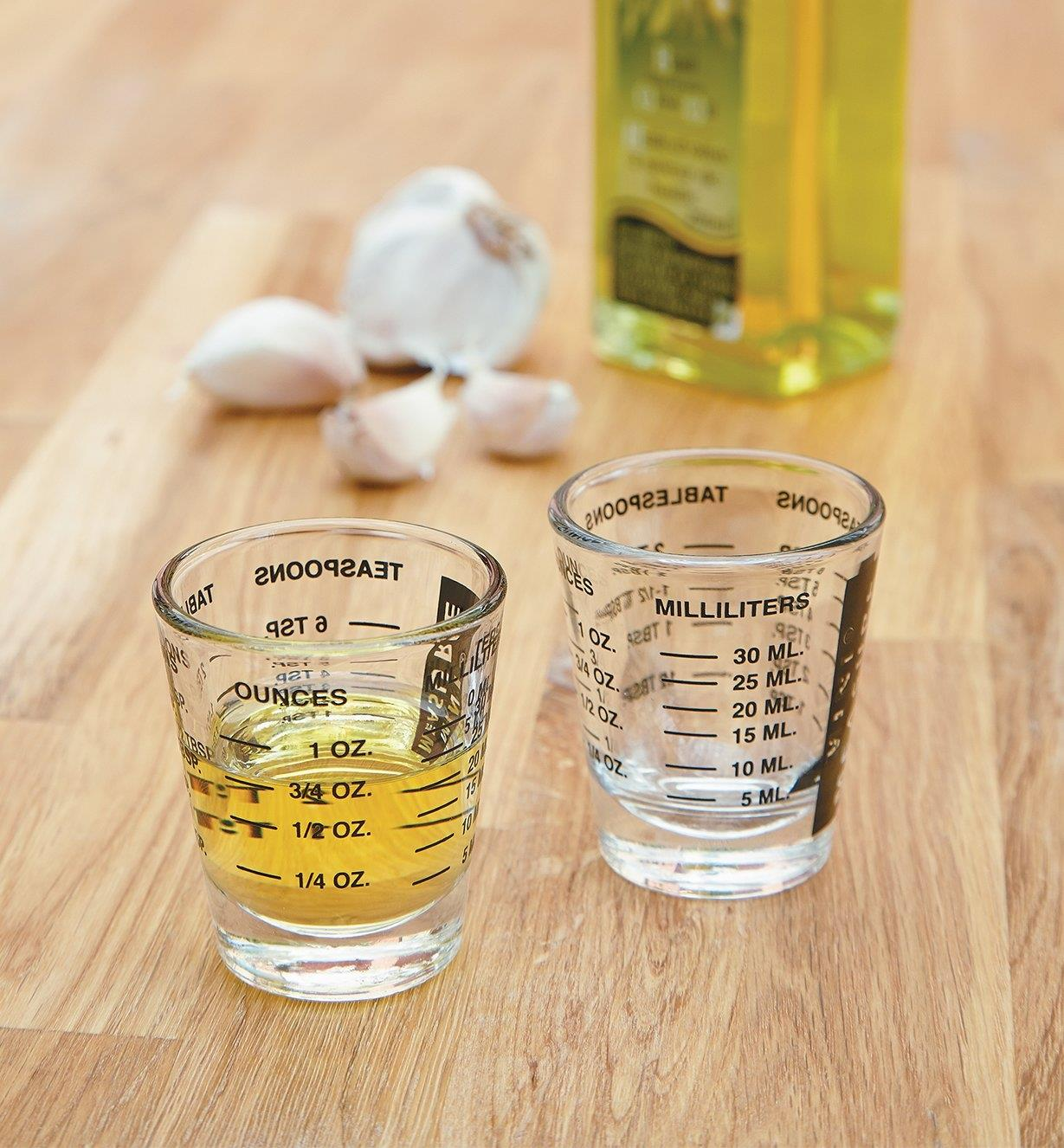Two Mini-Measures, one empty and the other half-full of oil, with oil and garlic in the background