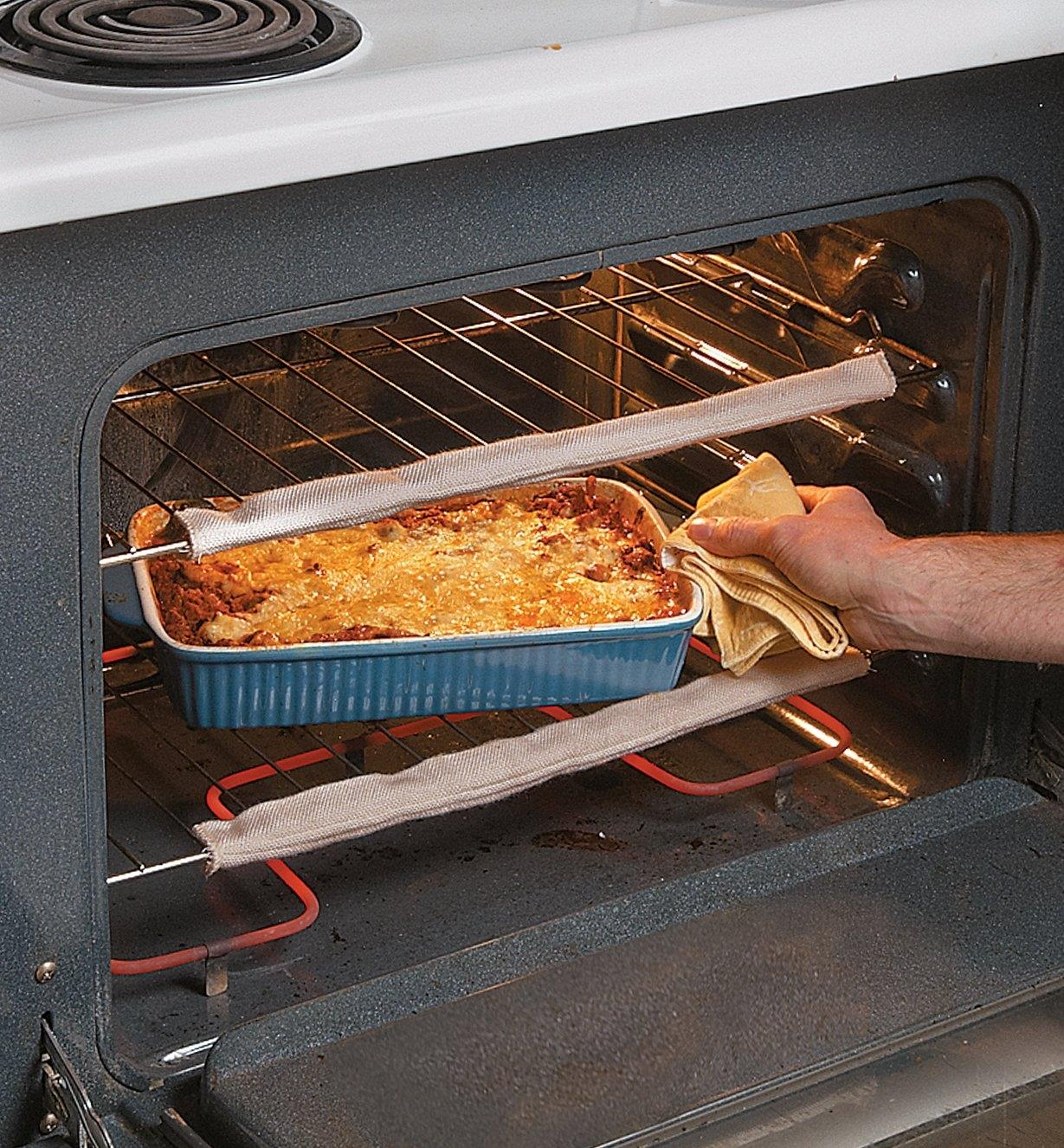 Removing a casserole from an oven with oven guards attached to the racks
