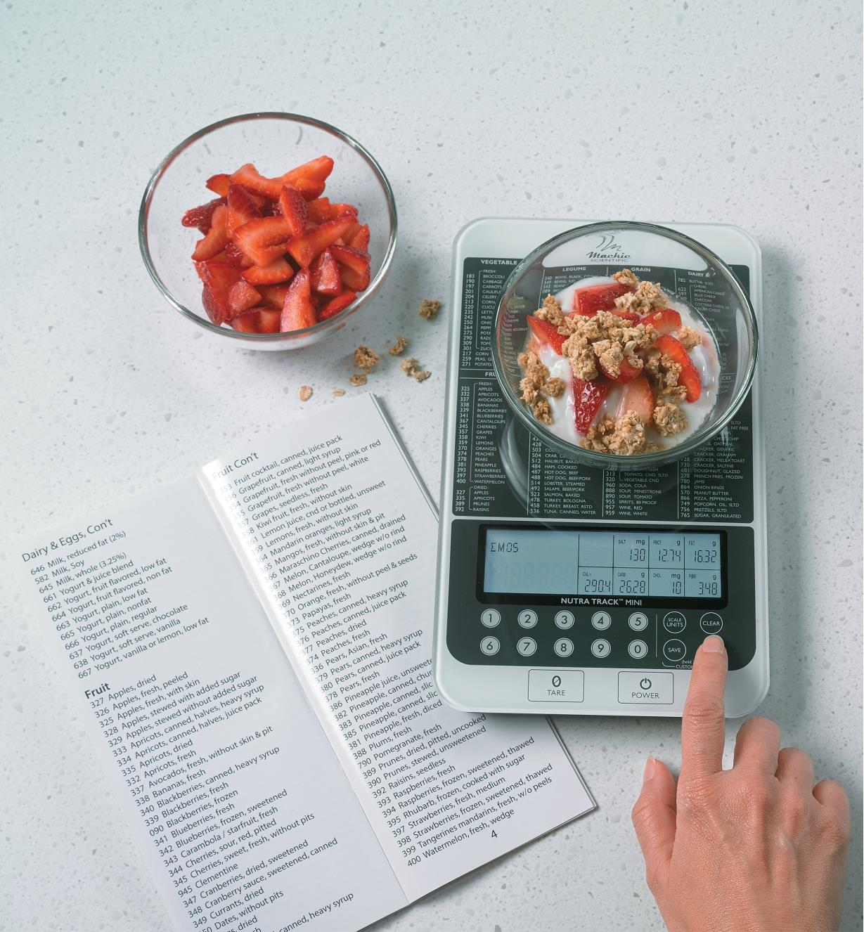Nutritional Scale weighing a bowl of granola and strawberries, with the guide lying open next to it