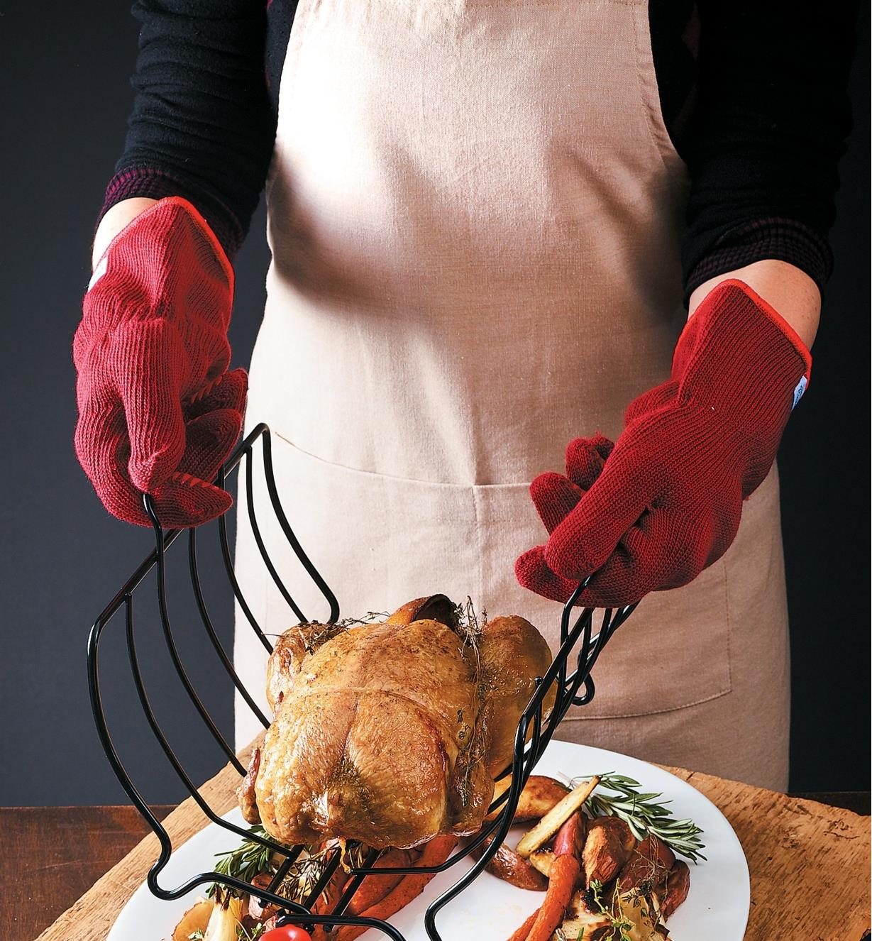 Oven gloves worn while handling a roasting rack