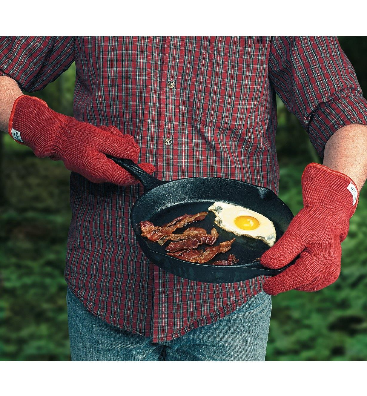 Oven gloves worn while handling a cast-iron frying pan
