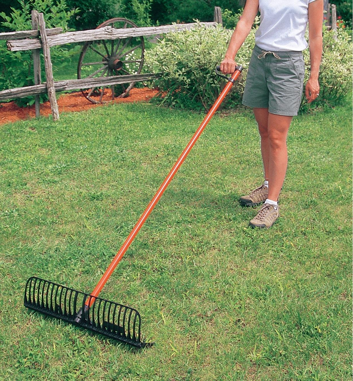 A woman uses a Power Rake with the handle turned sideways