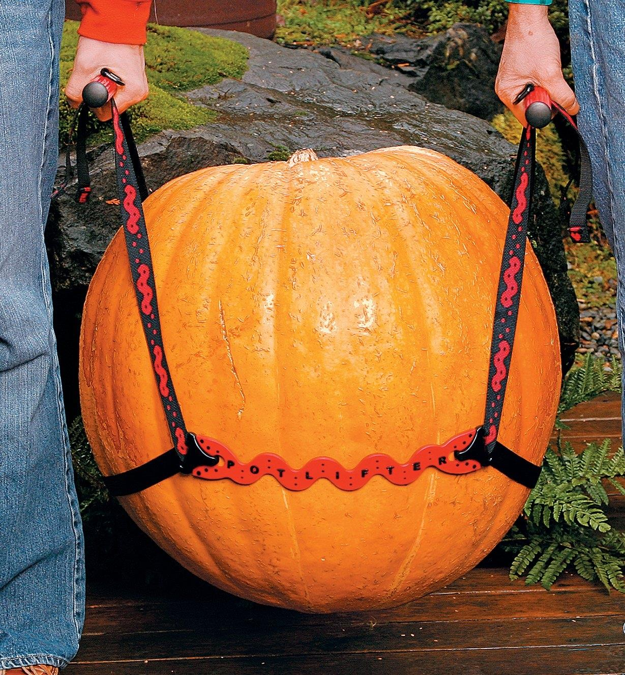 Two people using the PotLifter to carry a large pumpkin