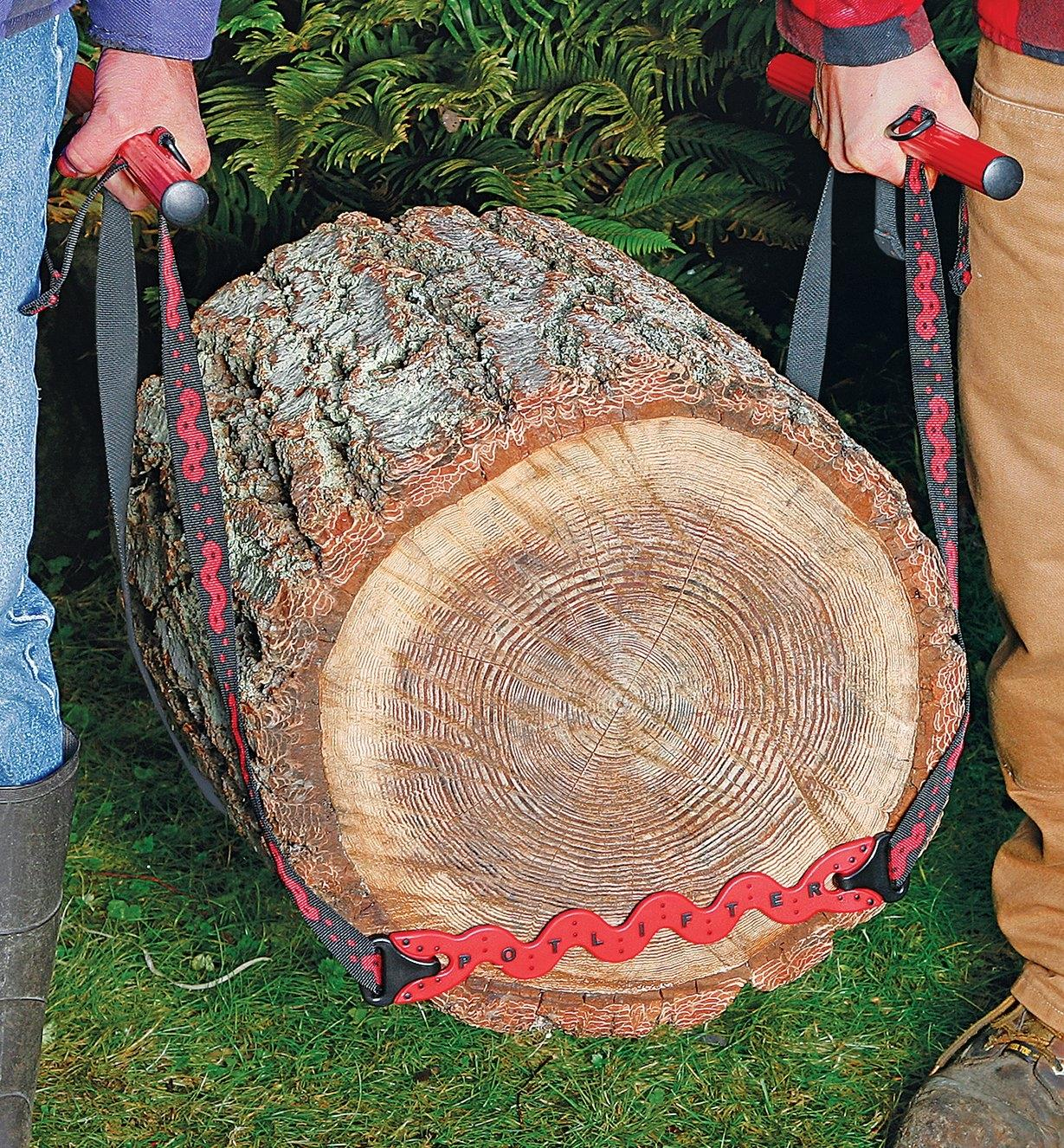 Two people using the PotLifter to carry a large log