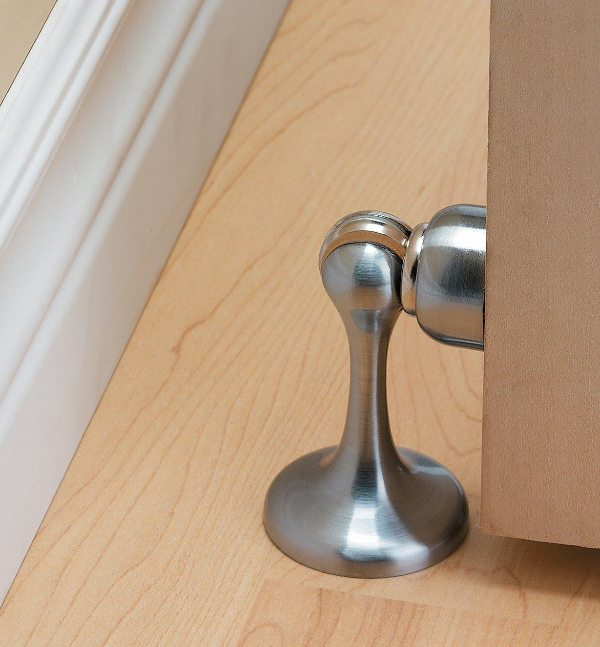 Satin chrome doorstop installed on a floor, holding a door open