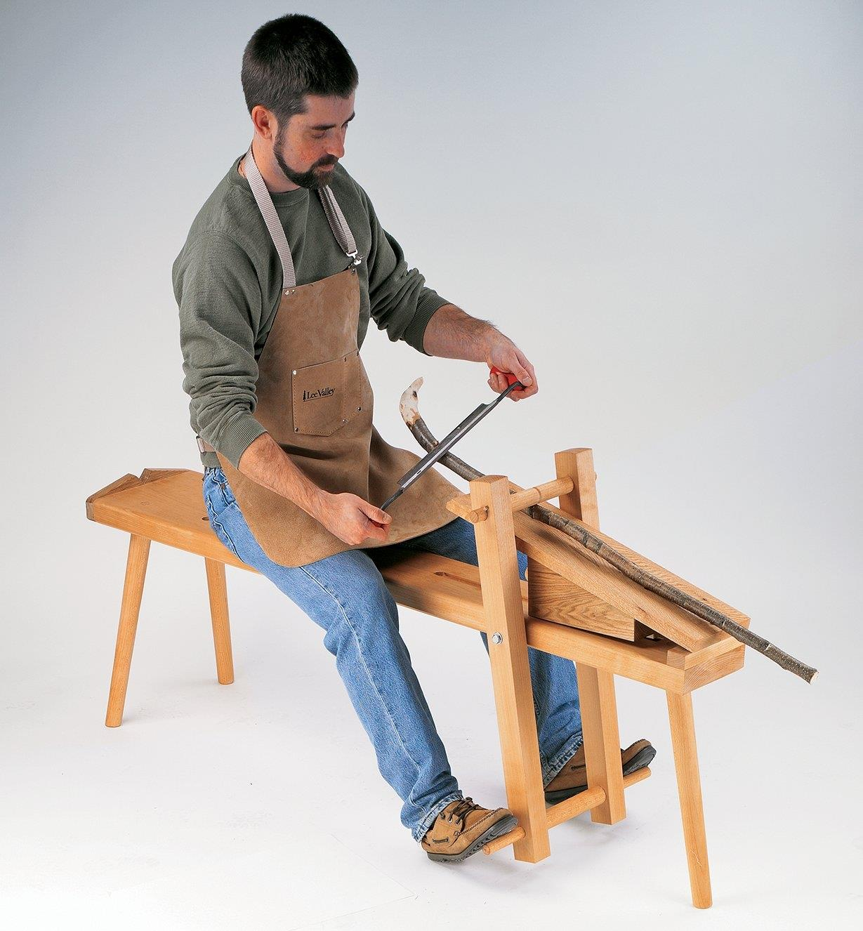 A man seated on a shaving horse uses a drawknife to shape a workpiece